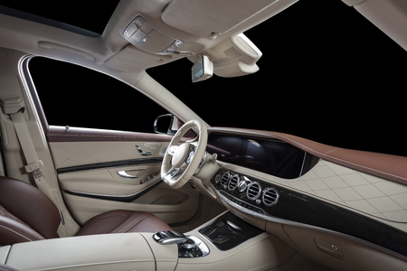 Car interior luxury. Beige comfortable seats, steering wheel, dashboard, climate control, speedometer, display, wood decoration, isolated on black, clipping path included