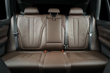 Beifahrersitze im modernen Luxusauto, Vorderansicht, rotes perforiertes Leder, einzeln auf Schwarz, Beschneidungspfad enthalten. Standard-Bild