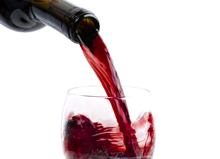 Pouring red wine into the glass against white background