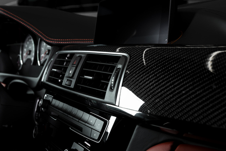 Close up of air condition panel in car modern interior with red and black leather and a carbon panel