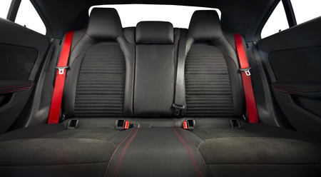 Back passenger seats in modern luxury car, frontal view, black leather, alcantara and red belts. Isolated Stock Photo