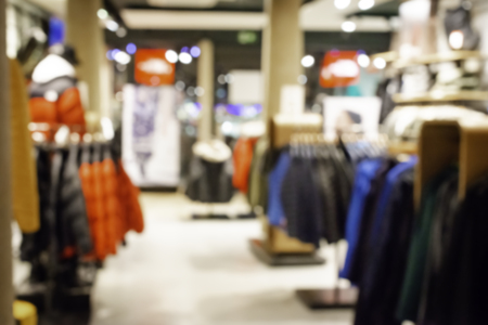 Blurred, defocused background of modern clothing store, abstract blurred fashion men shop background