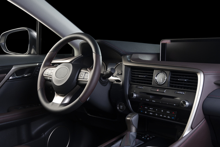 Car interior luxury. Beige comfortable seats, steering wheel, dashboard, climate control, speedometer, display, wood decoration, isolated on black Banco de Imagens