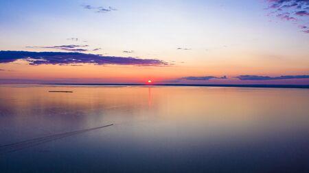 Sonnenuntergang Himmel Hintergrund. Dramatischer goldener Sonnenuntergang mit Abendhimmelwolken über dem See. Atemberaubende Himmelswolken im Sonnenaufgang. Himmelslandschaft. Panoramablick.