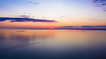 Sunset sky background. Dramatic gold sunset with evening sky clouds over the lake. Stunning sky clouds in the sunrise. Sky landscape. Panoramic view.