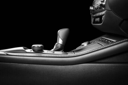 Modern luxury car Interior - steering wheel, shift lever and dashboard. Car interior luxury inside. Isolated over black background