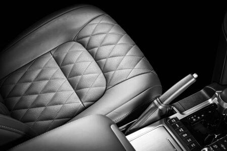Modern luxury prestige car interior, dashboard, steering wheel. Black  leather interior. Isolated over black backround
