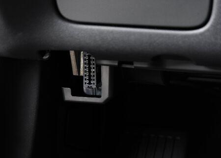 Automotive Electronic Diagnostic port OBD II under car dashboard Stock Photo