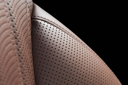 Comfortable leather seat. Red perforarated leather car seat isolated on black background with copy space