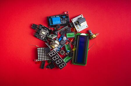 Micro electronics arduino DIY components over red  background, top view, copy space. Microcontrollers, boards, sensors, leds, controllers
