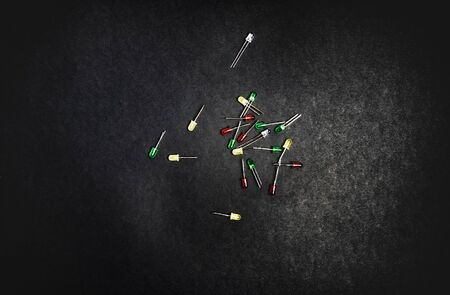 Small colorful LED diodes. Electroluminescent semiconductor light emitting source. Electrotechnical background. Red, blue, green or yellow transparent plastic electronic components