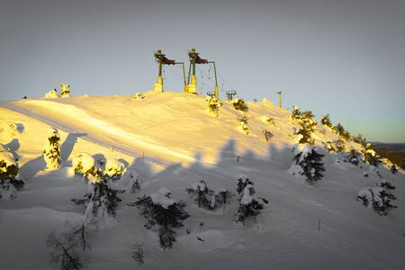 Peak of the mountain with a slope and ski lifters on the sun set 版權商用圖片