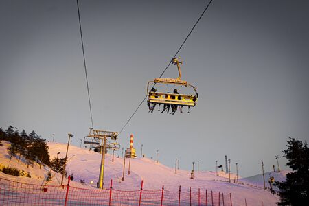Silhouettes of skiers on chair lifts in the evening, sunset 版權商用圖片