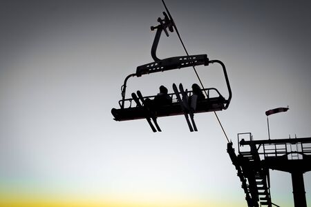 Silhouettes of skiers on chair lifts in the evening, sunset light