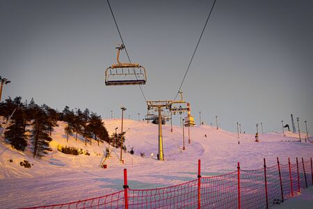 Silhouettes of skiers on chair lifts in the evening, sunset lights