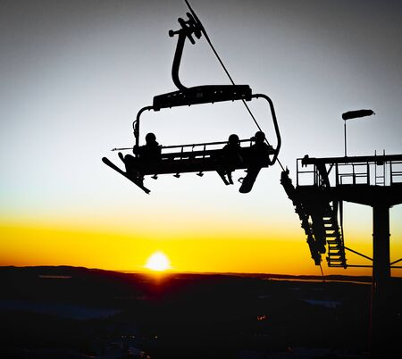 Silhouettes of skiers on chair lifts in the evening, sunset yellow light 版權商用圖片