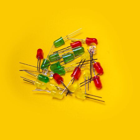 Small colorful LED diodes. Electroluminescent semiconductor light emitting source. Electrotechnical background. Red, blue, green or yellow transparent plastic electronic components over yellow