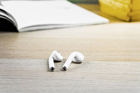 Modern white wireless headphones on wood table with opened book on the background Stock Photo