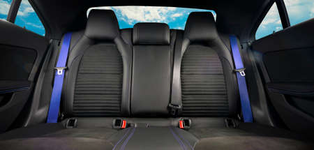 Back passenger seats in modern luxury car, frontal view, black leather, alcantara and blue safety belts