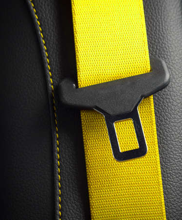 Modern race car black leather interior. Part of yellow leather car seat details. Safety belt close-up