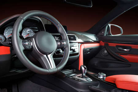 Modern luxury car Interior - steering wheel, shift lever and dashboard. Car interior luxury inside. Steering wheel, dashboard, speedometer, display. Red and black leather cockpit Banco de Imagens