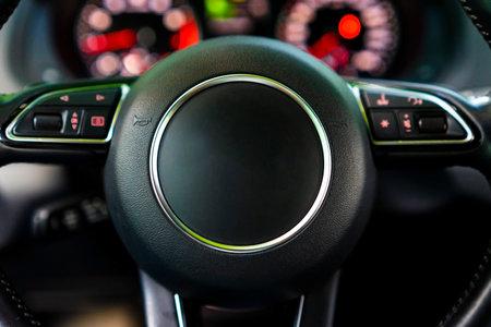 Modern luxury car Interior - steering wheel and blurred dashboard. Car interior luxury. Steering wheel, dashboard, speedometer, display. Standard-Bild