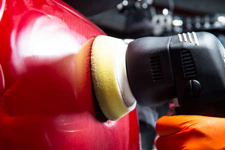Buffing and polishing car. Car detailing. Man holds a polisher in the hand and polishes the red car. Tools for polishing