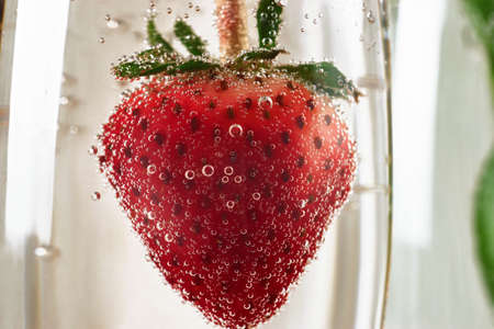 Strawberry inside a glass with champagne