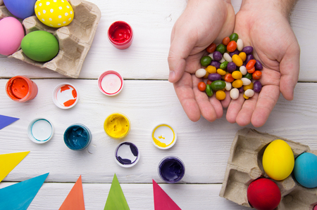 Hands holding candy, top view. Easter eggs, paint and easter holiday decoration