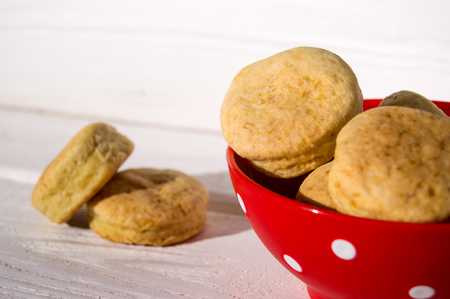 Baked homemade cookies in red plate on white wooden background