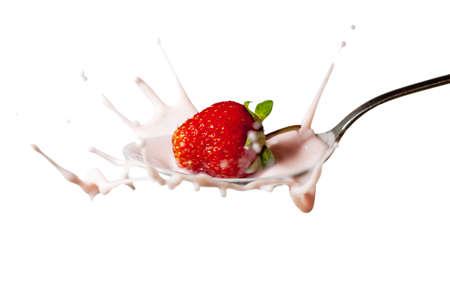 fresh strawberry splashing into the spoon full of yoghurt