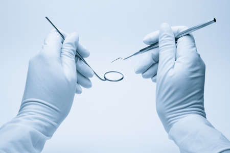 dentista: manos de dentista celebrar sus herramientas durante el examen de paciente  Foto de archivo