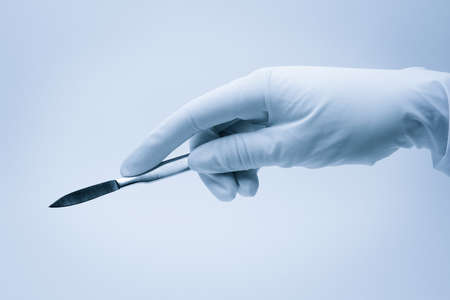 surgeon operating: hand of surgeon with scalpel during surgery Stock Photo