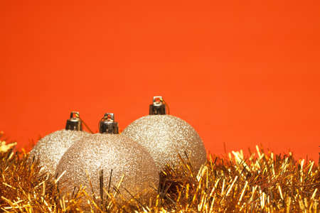 gold shiny christmas balls with tinsel over orange background Stock Photo - 8481835