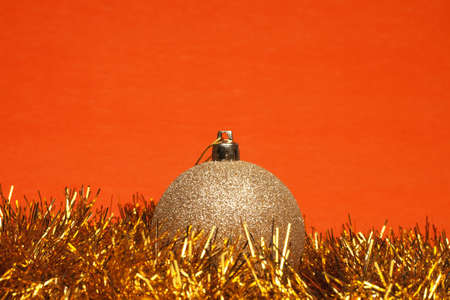 shiny christmas ball with tinsel over orange background Stock Photo - 8512604