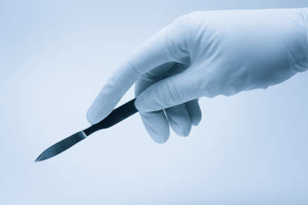 surgeon hand with scalpel during surgery Stock Photo