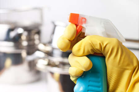 hand in protective glove holding spray. cleaning a kitchen concept