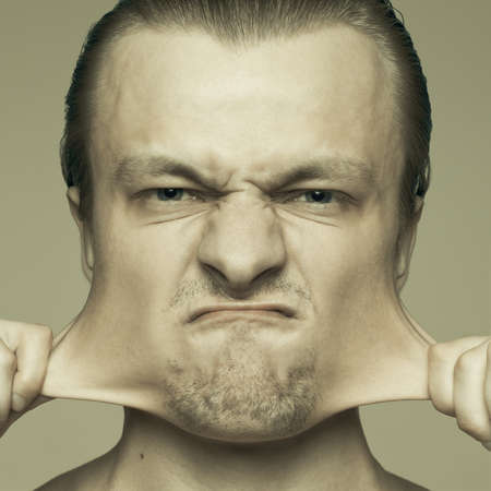 plasticity: portrait of man stretching out his cheeks Stock Photo