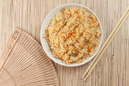 cooked rice with chopsticks and fan photo