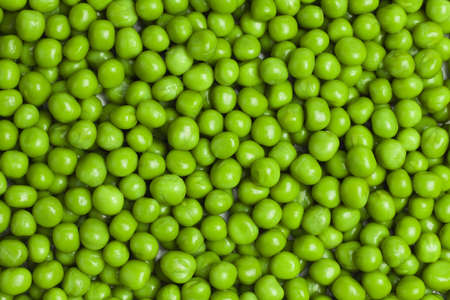 canned food: sweet green peas background Stock Photo