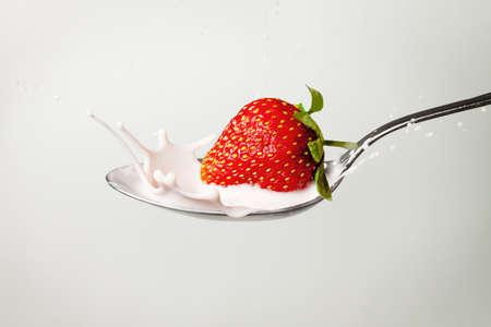 fresh strawberry splashing into spoon full of milk