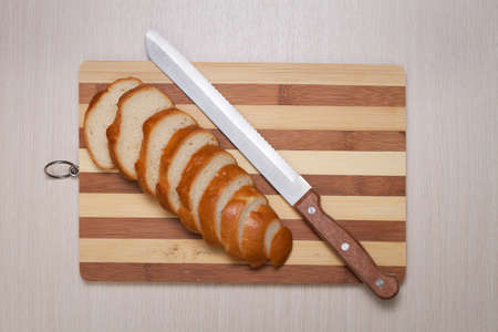sliced bread on breadboard and knife photo