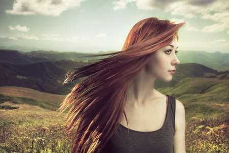beautiful girl upland with hair blown by wind photo