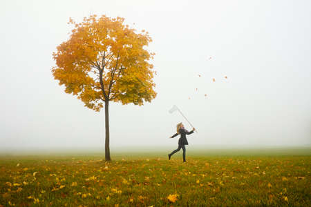 happy young girl catching autumn leafs with net photo
