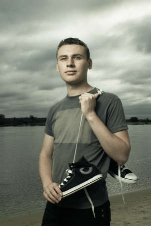standing water: portrait of young man standing on the river bank Stock Photo