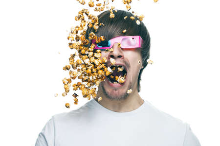 3d technology conceptual photo of young man in stereo glasses eating popcorn
