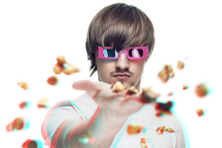 young man in stereo glasses throwing popcorn at the viewer 3d movie concept photo
