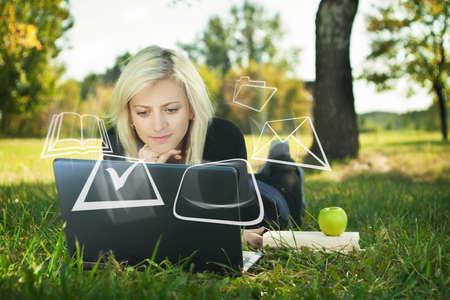 Studentin studiert in Park mit Laptop Standard-Bild