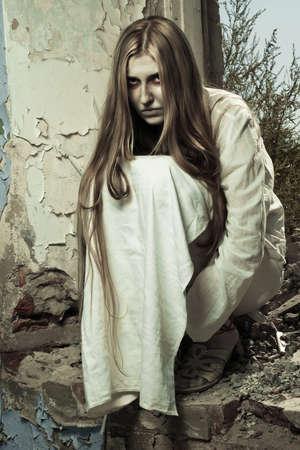 Zombie-Mädchen sitzen in verlassenen Gebäude