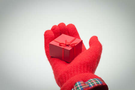 hand giving red box with present over grey photo
